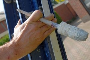 Exterior painters and decorators Swansea climbing ladder with brush in hand